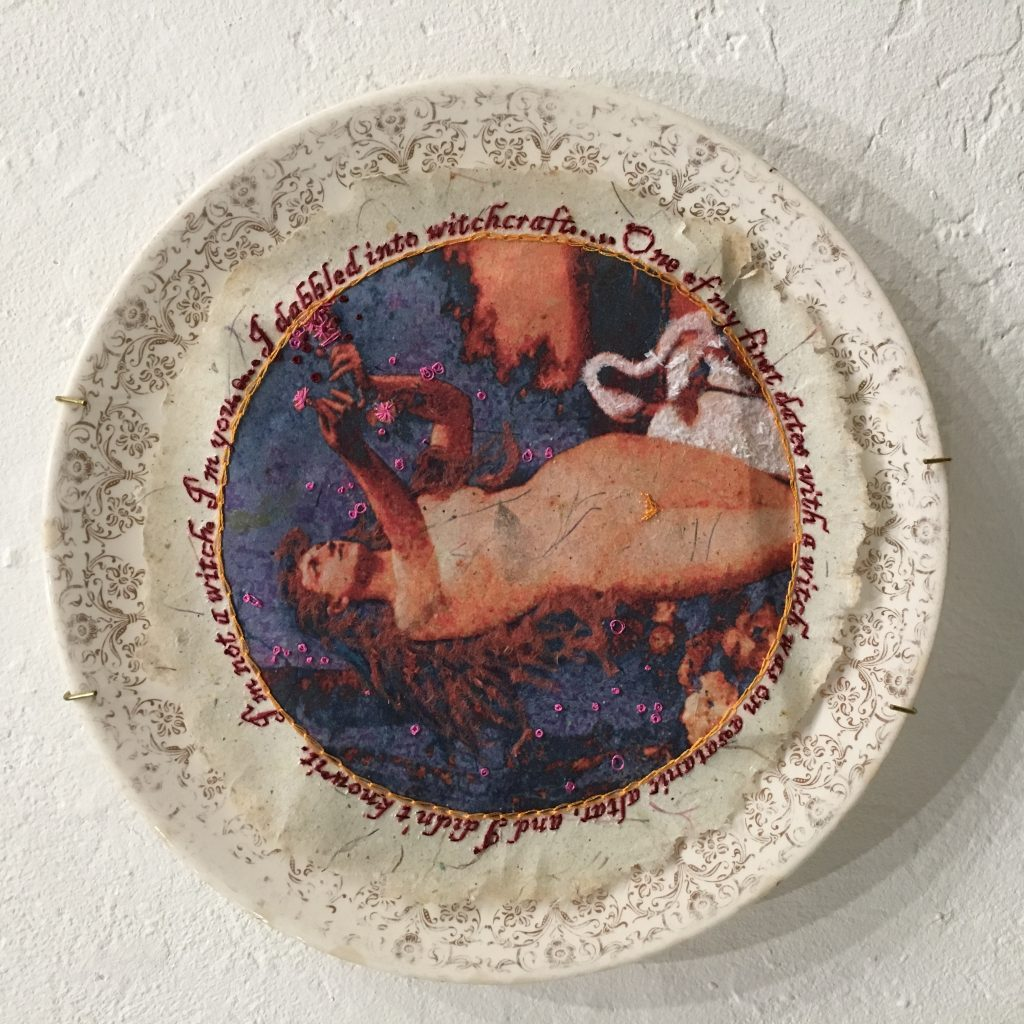 "GINI HOLMES I am not a witch, 2017 Heat transfer on handmade paper, embroidery, ink, flocking, dinner plate $207  Quote: ""I'm not a witch… I'm you."" ~ Christine O'Donnell, in a 30 second ad responding to a video clip from a 1999 appearance in Bill Maher's ""Politically Incorrect"", in which she said, "" dabbled into witchcraft I never joined a coven. But I did, I did… I dabbled into witchcraft. I hung around people who were doing these things. I'm not making this stuff up. I know what they told me they do… One of my first dates with a witch was on a satanic altar, and I didn't know it. I mean, there's little blood there and stuff like that. We went to a movie and then had a midnight picnic on a satanic altar.""  Image: Hymn To The Creator"