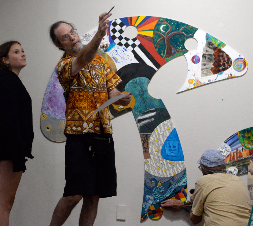 "Artists Olive Sisk, Titus Woods and David Sisk, AKA "" Sisko""  left to right work to assemble a ""Puzzle Show"" at the Chico Art Center in Chico Calif. Friday June 8, 2018. The piece is made from over 320 puzzle pieces by many artists. (Bill Husa -- Enterprise-Record)"