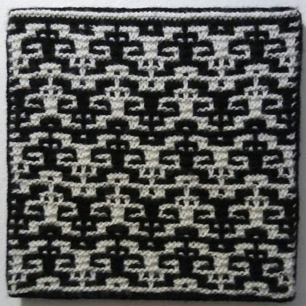 "TK Frankenber, ""Hand in Hand"", 100% Wool, Knitted Shadow Mosaic, 12"" square, $60		Knitted Shadow Mosaics are interlocking and inverted motifs in opposite and reversing shades. Walking through a local gallery provided the inspiration."