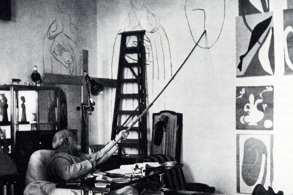 A debilitated Matisse draws from his bed using an improvised staff, ca. 1940