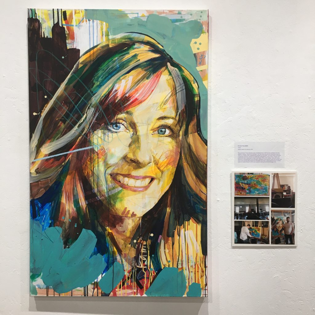 "DYLAN TELLESEN, ""Tania"", mixed media on canvas, NFS.  This portrait of Tania Heyman was commissioned in 2019 by her husband and two children; Nathan, Alexis and Nicholas. Not only does the portrait beautifully capture Tania, its creation was a therapeutic process for the family. All three family members, in separate sessions, worked to create the underpainting using colors, images and words that were meaningful to them and Tania. If you look closely, there are areas where the underpainting shows through. Working in this manner made this project that much more emotionally intense for the family and artist. Tania experienced a sudden onset of mental illness in 2012 and ended up taking her life at the age of 44."