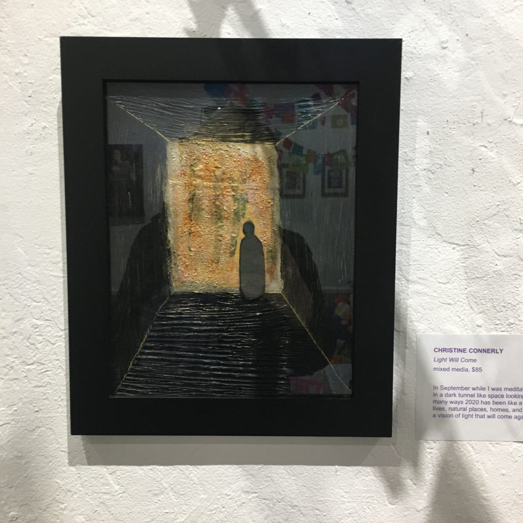 "CHRISTINE CONNERLY, ""Light Will Come"", mixed media, $85. In September while I was meditating, I had a vision of a figure standing in in a dark tunnel like space looking out on a rectangle of golden light. In many ways 2020 has been like a dark tunnel full of grieving for the loss of lives, natural places, homes, and civil discourse. Making art has given me a vision of light that will come again in the future."