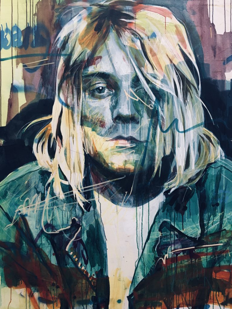 "DYLAN TELLESEN, ""Kurt Cobain"", mixed media, $2,400.  Best known as the guitarist, primary songwriter and frontman of the rock band Nirvana, Kurt Donald Cobain (February 20, 1967 – April 5, 1994) was an American singer-songwriter and musician. Through his angst-fueled songwriting and anti-establishment persona, Cobain's compositions widened the thematic conventions of mainstream rock music. He was often heralded as a spokesman of Generation X and is considered to be one of the most influential musicians in the history of alternative rock."