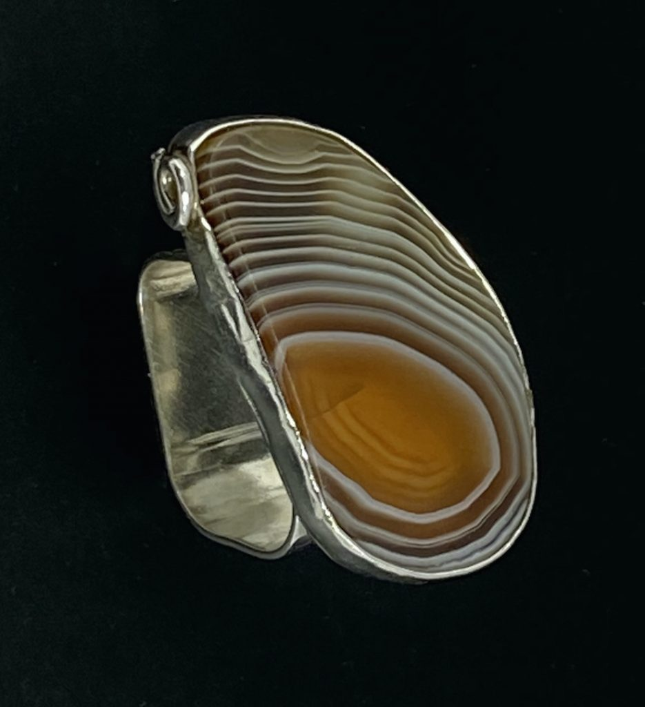 "Joan	North, ""Cyclone"", Botswana agate & sterling, size 8. $150.	I like shapes that remind me of life situations (my ""Metaphors in Metal"" series, for example), starkly simple shapes, and combinations that draw your surprised eye. I love contrast in form and similarity in color. Incorporating stones into metal designs delights me. I dream of new designs, smiling in my sleep. Most of all, I want each piece to intrigue the viewer."