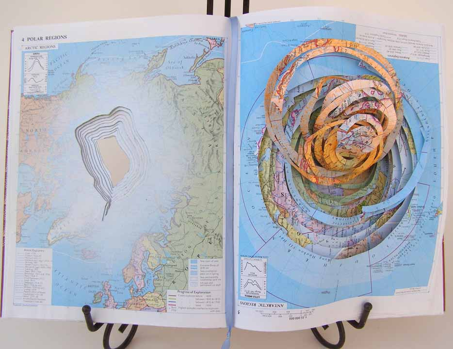 "Claudia Berlinski, Separate But Equal, 2011, Mixed media, 12"" x 18"" x 3"", $250.  Separate But Equal was created in response to the climate crisis and the idea that global warming is creating devastating changes in the environment. I utilized an atlas for this project, focusing on the pages showing the arctic region and Antarctica to depict two different kinds of environmental disasters. Each page is modified through additive and subtractive processes and the addition of color. The book is displayed with a book stand."
