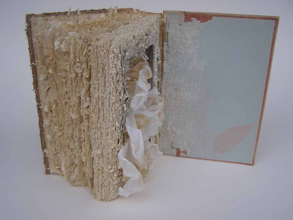 "Claudia Berlinski, Speechless, 2012, Altered book with used coffee filters, 8"" x 10"" x 3"", $250.  Speechless grew out of a repetitive cathartic striking of the book using an art knife during a particularly difficult period in my life. After passing through this period I created the flower-like forms that emerge from the tattered book as an analogy for surviving and healing after that experience."