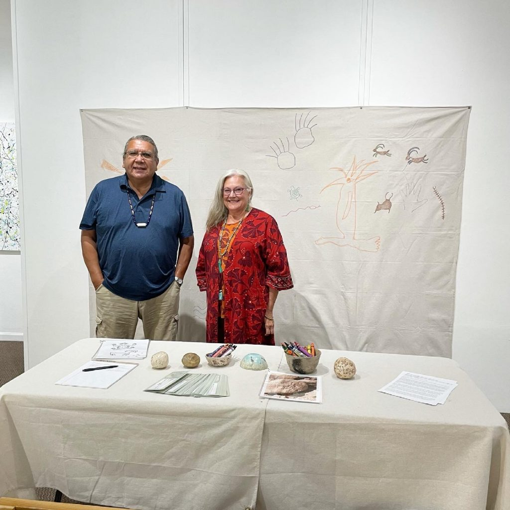 """Lucky Preston and Kim Preston standing in front of their interactive project, """"Newspaper Rock"""", 2021, This interactive display invites the visitor to draw on the canvas and tell a story through symbols and designs. We recognize the cultural and creative value of these artifacts. Our ceramic pieces: totem, rattles and bowls depict petroglyph images of actual rock art found worldwide. Rock art is found throughout the world in deserts, forests and caves. Vandals have defaced and ruined a great many of these delicate images, by scratching, gouging, chiseling or painting over them."""