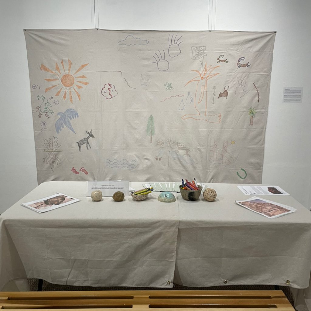 """""""Newspaper Rock"""", 2021, This interactive display invites the visitor to draw on the canvas and tell a story through symbols and designs. We recognize the cultural and creative value of these artifacts. Our ceramic pieces: totem, rattles and bowls depict petroglyph images of actual rock art found worldwide. Rock art is found throughout the world in deserts, forests and caves. Vandals have defaced and ruined a great many of these delicate images, by scratching, gouging, chiseling or painting over them."""