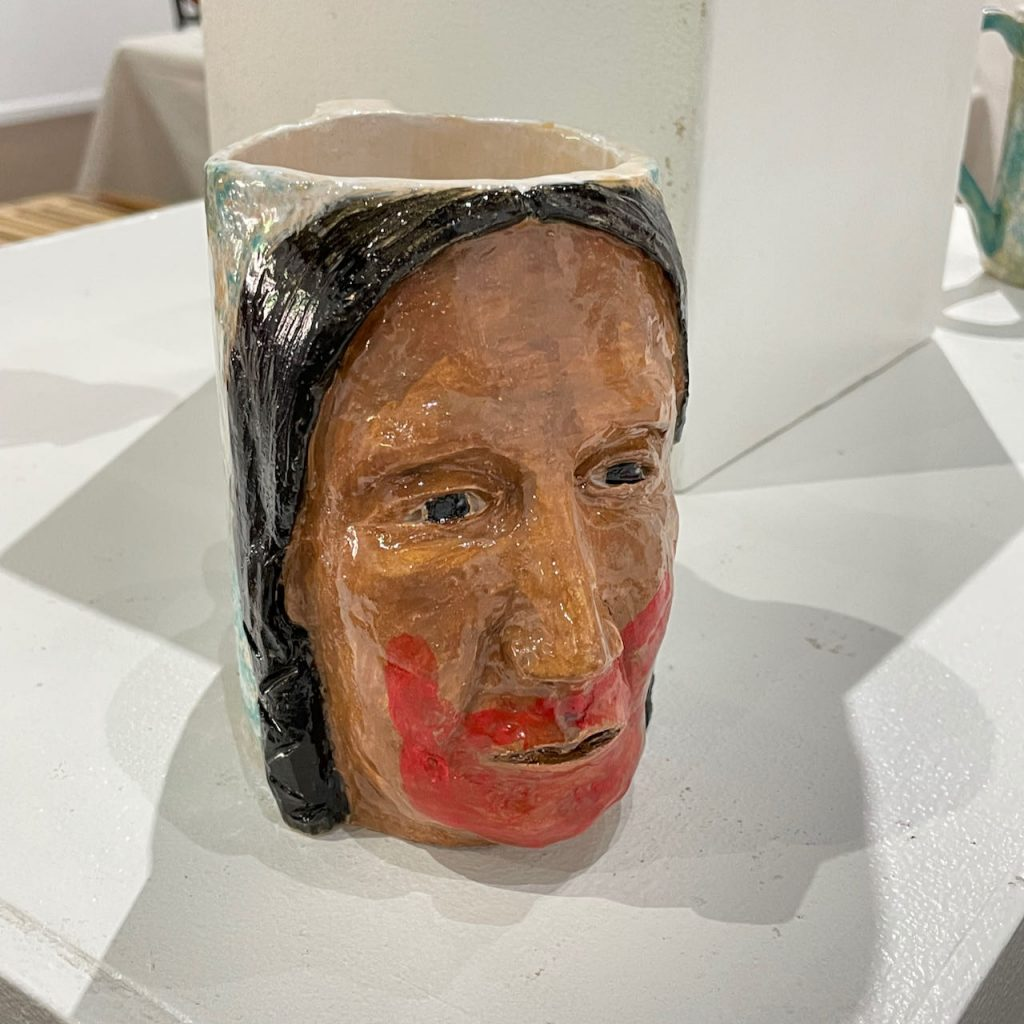 """Lucky Preston, """"Missing and Murdered Indigenous Women"""", 2021, Ceramic and mixed media.  These pieces carry the red handprint over the mouths to draw attention to the """"Silent-No-More"""" of the Missing and Murdered Indigenous Women Movement. For decades throughout the world, thousands of Indigenous women and girls have disappeared without a trace and without follow-up by the authorities, leaving families heartbroken.  The Red-Hand icon serves to bring awareness to the issue. Recently, President Biden declared May 5th as Murdered and Missing Indigenous Women Awareness Day."""