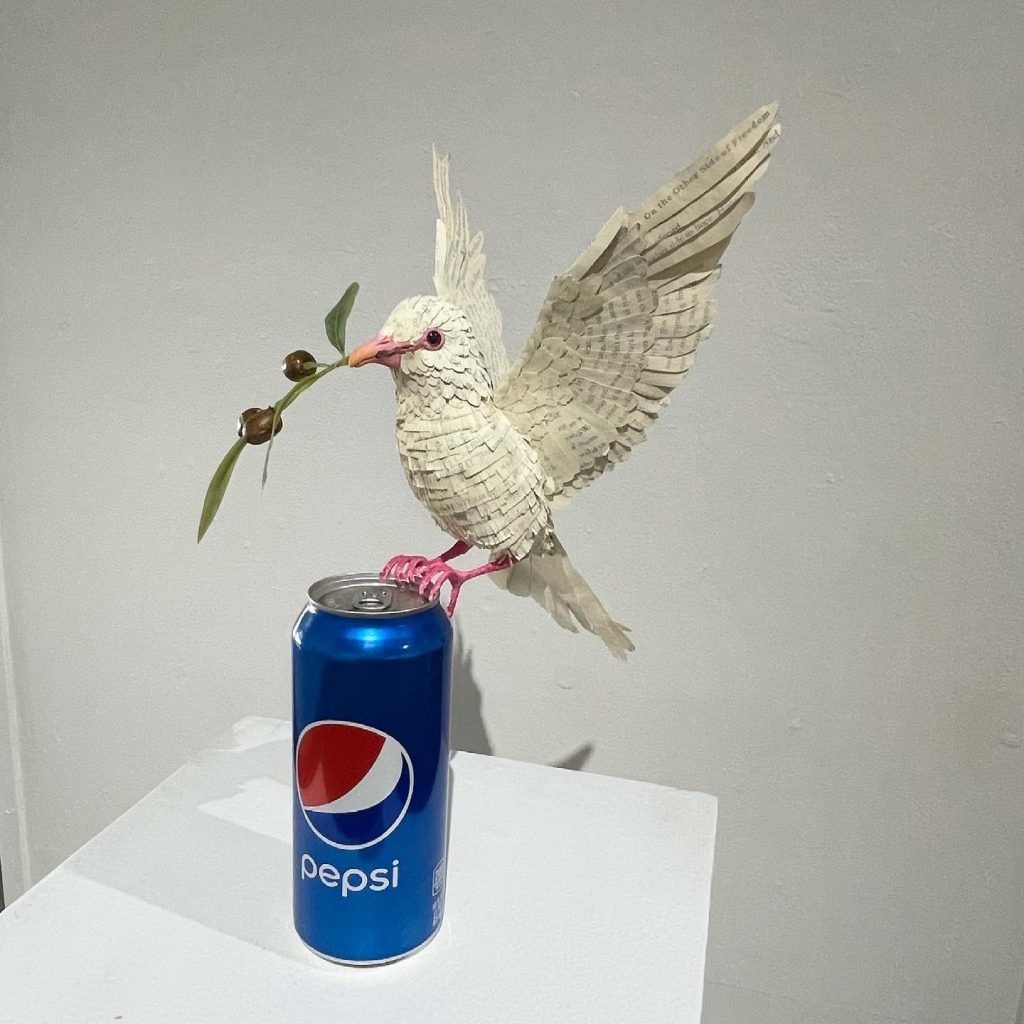 """Christian Victoria Davila, """"That's all it took"""", 2021, 3D printed polymer armature, laser cut book pages from """"On the Other Side of Freedom"""" by DeRay Mckesson, Pepsi can, $200 -   Pepsi's 2017 ad about BLM Protest was very tone deaf. The ad quickly became a multitude of memes, with phrasing such as """"when the cops come and you only got Coca-Cola in the fridge"""" with an image of Malcom X peeking through the window with a gun. That's All It Took is my take or meme on Pepsi's commercial."""